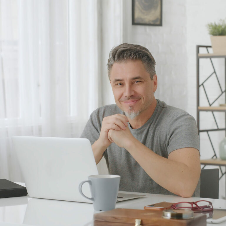 Happy older man with gray hair working at home in home office with laptop computer.